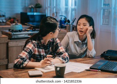 young female business woman back to home in late night sitting at home kitchen table while roommate using laptop computer to calculate bills. two asian ladies gossip chatting talking in midnight.