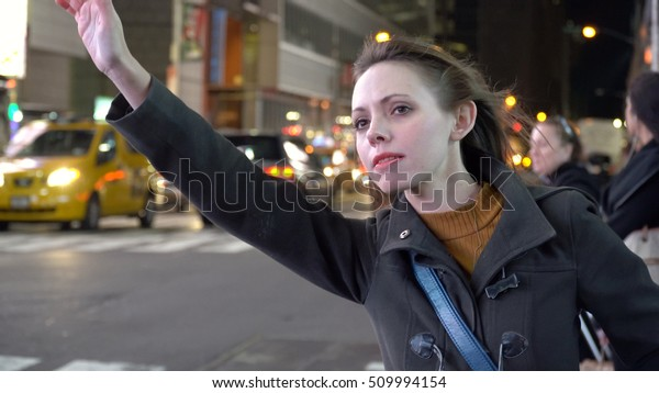 Young female business woman hail cab New York City at night. Hipster startup company executive Attractive smile tourists walk in crosswalk background, downtown Manhattan. Taxi car traffic bokeh effect