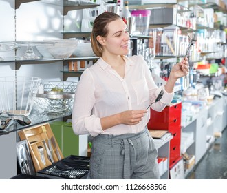 Young female buying flatware in the cookware section at store