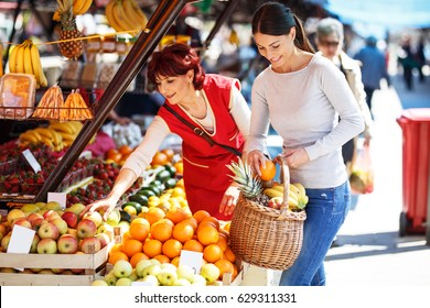 Young female buys fruits on street market.Saleswoman help her to choose fresher fruit.