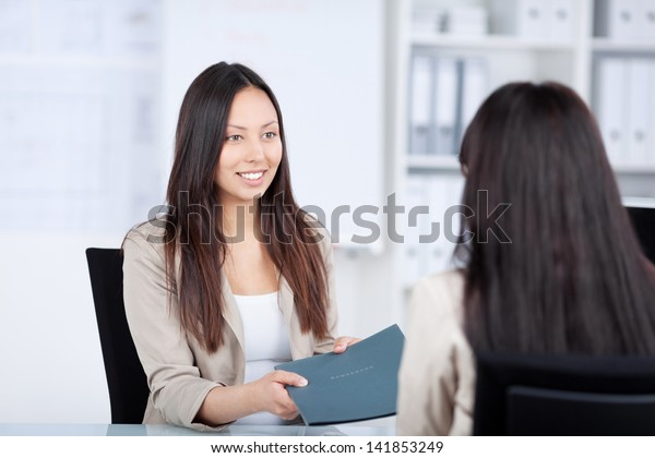 Young female candidate giving file to businesswoman at office desk