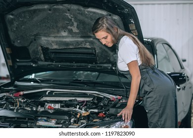 Young female from car service in a black jumpsuit and white t-shirt standing near the broken car. The girl opened the hood and looked at the engine. Refit woman car