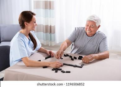 Young Female Caretaker Looking At Elder Man Playing Dominoes On Desk