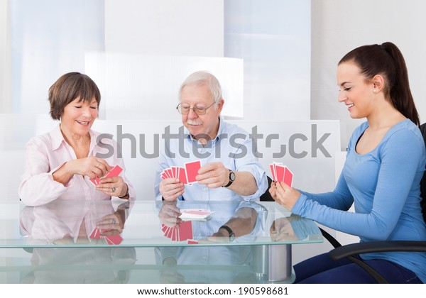 Young female caretaker playing cards with senior couple at table in nursing home