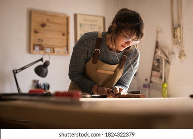 A young female carpenter working as wood designer in a small carpentry workshop. Young business woman handcrafting a piece of timber and designing new house furniture. Entrepreneurs concept lifestyle - Shutterstock ID 1824322379