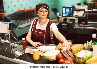 Young female cashier in uniform thoughtfully looking on products working in modern supermarket