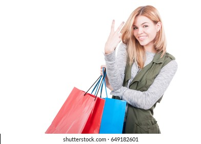 Young female in casual clothes carrying shopping bags and counting two fingers on white background with text space