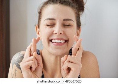 Young female Caucasian student keeping her fingers crossed and eyes closed to make a desired wish. Charming white smile, positive heartwarming look of girl sincerely believing in her victory.