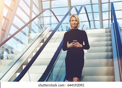 Young female CEO with mobile phone in hands, is using moving staircase in modern interior for change the floor in skyscraper office. Businesswoman with cell telephone in hands is looking at camera