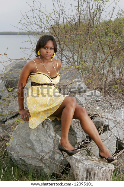 a young female from Chad Africa sitting on large rocks