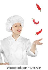Young female chef catching chilli peppers