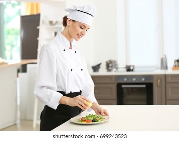 Young female chef dressing salad with lemon juice in kitchen