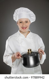 Young female chef holding stainless steel pot