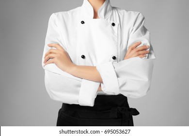 Young female chef on light background