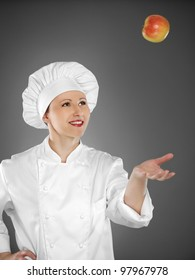 Young female chef playing with apple