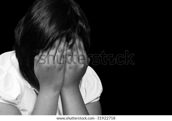 A young female child is covering her face and crying, post processed in black and white and isolated against a black background