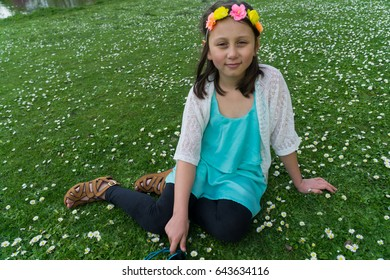 Young female child relaxing in a daisy field in a park in the springtime