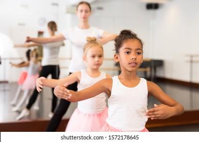 Young female classical dance teacher helping her little girls students in ballet class