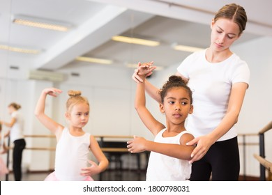 Young female classical dance teacher helping her little girls students in ballet class