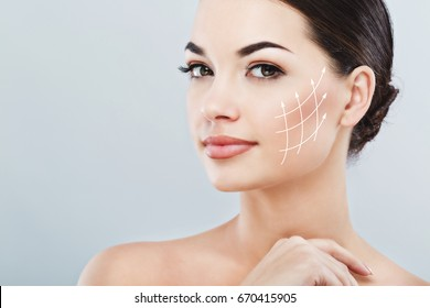 Young female with clean fresh skin, antiaging concept. Attractive girl with naked shoulders, looking at camera and smiling, holding hands near face, lifting arrows lattice
