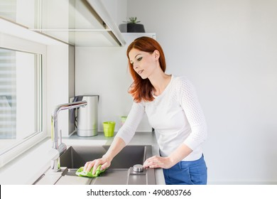 young female cleaning kitchen
