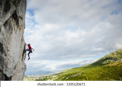 Young female climber hanging by a cliff