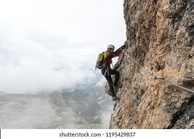 young female climber on a vertical and exposed rock face climbing a Via Ferrata