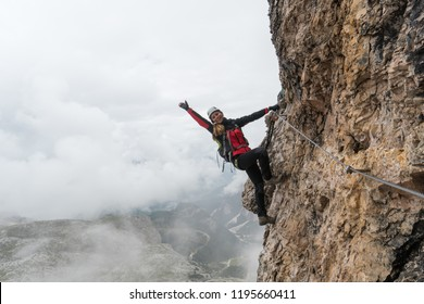 young female climber on a vertical and exposed rock face climbing a Via Ferrata and waving