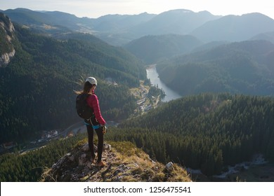 Young female climber standing in awe and admiring a lake in Romania (Lacu Rosu) at the end of Wild Ferenc via ferrata route