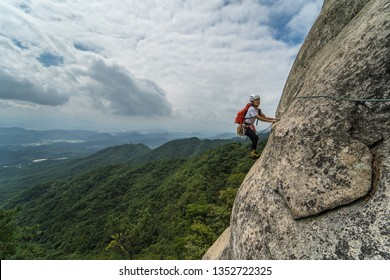 A young female climber traverse the cliff. rock climbing