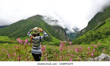 Young female climber walking down grassy rocky hill in green beautiful mountains in india. Woman tourist breathtaking view amazing nature healthy lifestyle,valley of flower,india