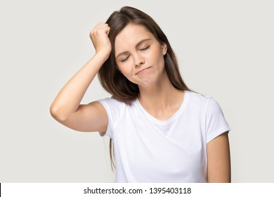 Young female closed eyes touches head with hand forgot something important she regrets about mistake feels stressed isolated on grey background studio shot, bad memory absent-mindedness concept image
