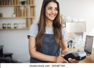 Young female coffee shop employee using a credit card reader and a laptop to bill the customer