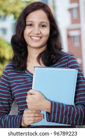 Young female college girl holding books