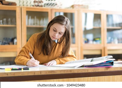Young female college student in chemistry class, writing notes. Focused student in classroom. Authentic Education concept.
