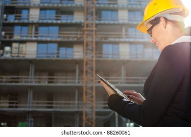 Young female construction specialist reviewing blueprints at construction site