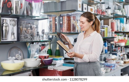 Young female consumer with kitchen scale  in the household store