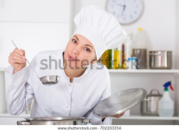 Young female cook tasting food while preparing in kitchen