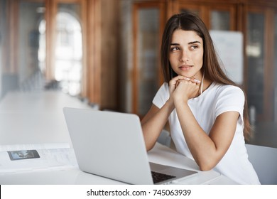 Young female copywriter using a notebook computer to write an article thinking about new book or magazine publication.