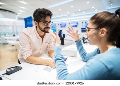 Young female costumer in electronic store talking to salesman.