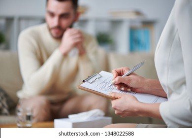 Young female counselor with pen filling in medical paper during individual session with one of patients