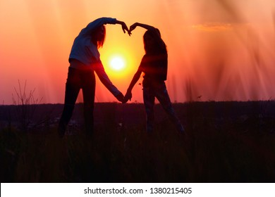 Young Female Couple Making Heart Shape With Hands At Sunset. Abstract Love Background. People, Love, Friendship Background. Female Best Friends Making A Heart.
