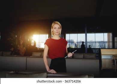 Young female creative designer holding touch pad while standing in modern interior, beautiful successful businesswoman posing with digital tablet while waiting for a partners in luxury restaurant