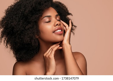 Young female with curly hair enjoying softness of clean face with closed eyes after skin care procedure against brown background