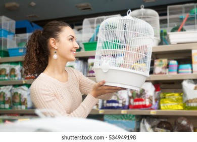 Young female customer buying cage for hamster in petshop