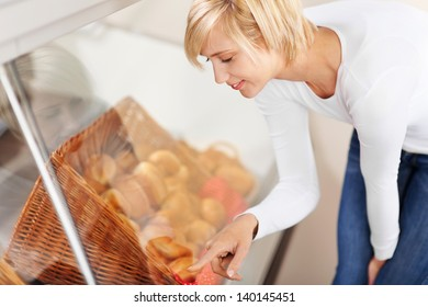 Young female customer choosing bread from display cabinet in cafe