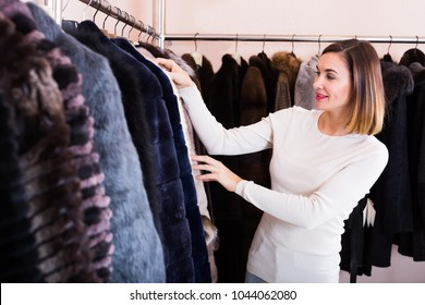 Young female customer examining best fur coats in women`s cloths store