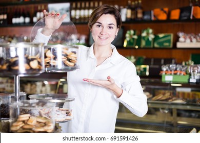 Young female customer examining desserts in confectionery