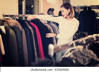 Young female customer examining red woolen coat in womens cloths store
