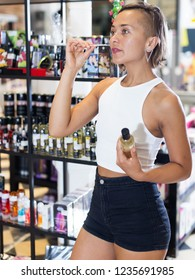 Young female customer looking bottle of pheromones in the sexshop